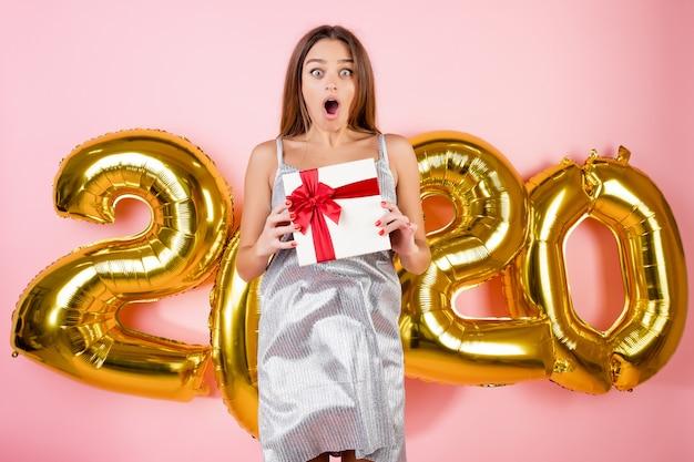 Kobieta skacze w powietrzu z pudełko przed 2020 świątecznych balonów na białym tle nad różowym