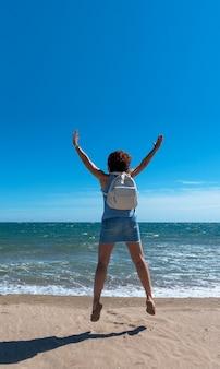 Kobieta skacze z radości na plaży w słoneczny dzień