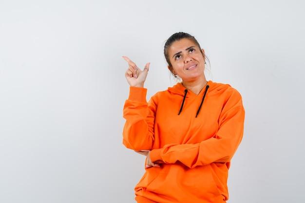 Kobieta skierowana w górę w pomarańczowej bluzie z kapturem i wyglądająca na marzycielską