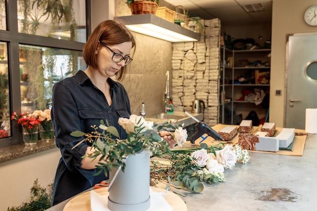 Kobieta sklepikarz, organizator ślubów pracuje z kwiatami, aby stworzyć bukiet kwiatów.