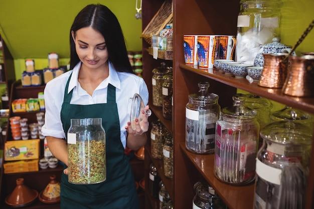 Kobieta sklepikarz trzyma słoik z przyprawą