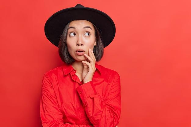 Kobieta skoncentrowana na niesamowitej ofercie lub reklamie, oszołomiona niespodziewaną rewolucją, nosi stylowe pozy w czerwonym studio
