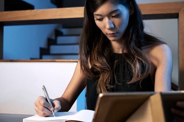Kobieta skoncentrowana na odrabianiu lekcji