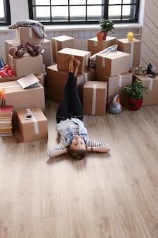 Kobieta skończyła pakowanie ładunków i leży z powrotem na podłodze