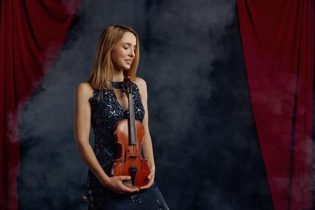 Kobieta skrzypek trzyma skrzypce w stylu retro. kobieta ze strunowym instrumentem muzycznym, sztuka muzyczna, muzyk gra na altówce