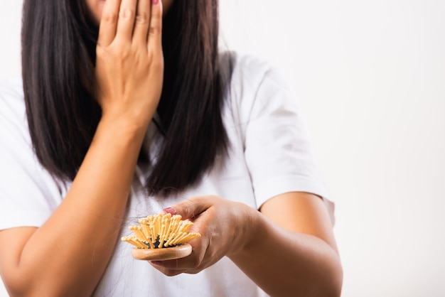 Kobieta słabe włosy problem jej trzymać szczotka do włosów z uszkodzonymi długimi włosami wypadającymi w grzebieniu na rękę