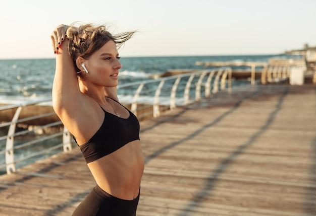 Kobieta slim fit robi rozciąganie dłoni przed ćwiczeniami na plaży o wschodzie słońca