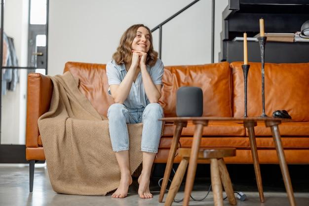 Kobieta słucha kolumny asystenta audio siedzącego na kanapie