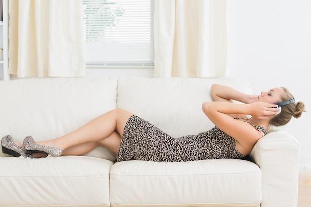Kobieta słucha muzyka na kanapie