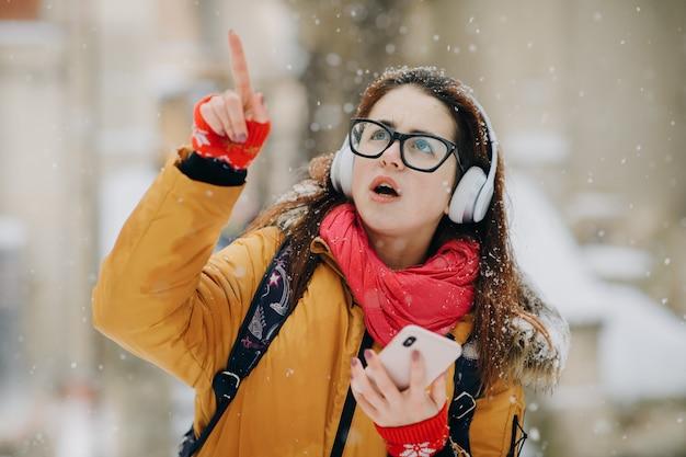 Kobieta słucha muzyka outside w zimie. drzewa w śniegu. chmura śnieg pogoda
