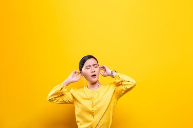 Kobieta słucha muzykę na odosobnionej kolor żółty ścianie z słuchawkami