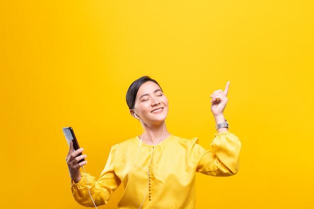 Kobieta słucha muzykę od smartphone na odosobnionej kolor żółty ścianie z słuchawkami