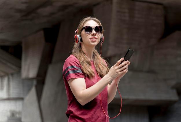 Kobieta słucha muzykę z okularami przeciwsłonecznymi
