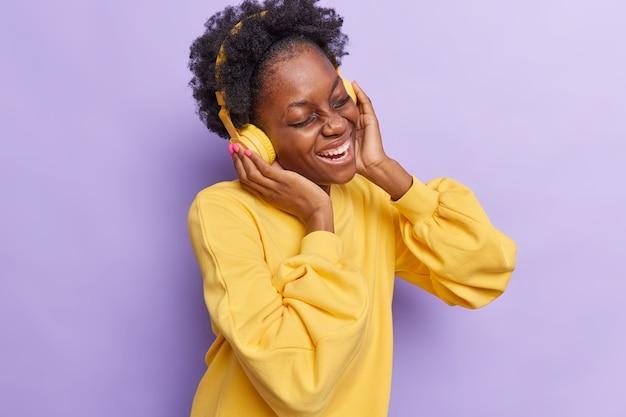 Kobieta słucha muzyki przez słuchawki ubrana w żółty sweter na fioletowym tle