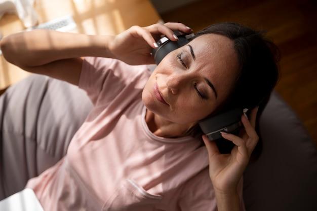 Kobieta słucha muzyki przez słuchawki w domu
