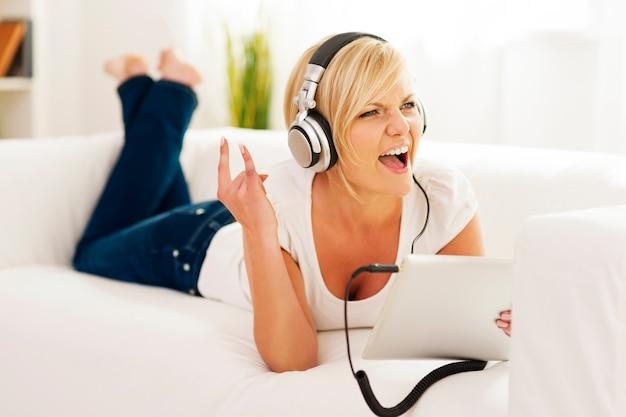 Kobieta słucha muzyki rockowej w domu