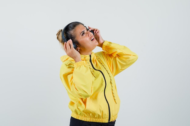 Kobieta słucha muzyki w słuchawkach w sportowym garniturze i marzycielski wygląd. przedni widok.