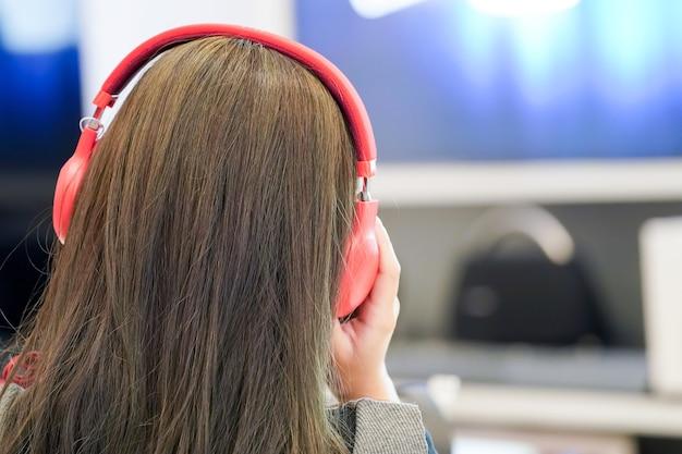 Kobieta słucha muzyki z czerwonym zestawem słuchawkowym.