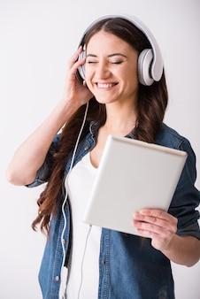 Kobieta słucha muzyki za pomocą tabletu i słuchawek.
