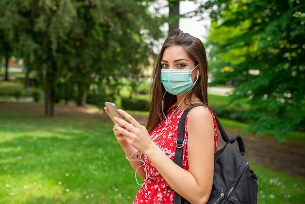 Kobieta słuchająca muzyki w parku podczas pandemii koronawirusa