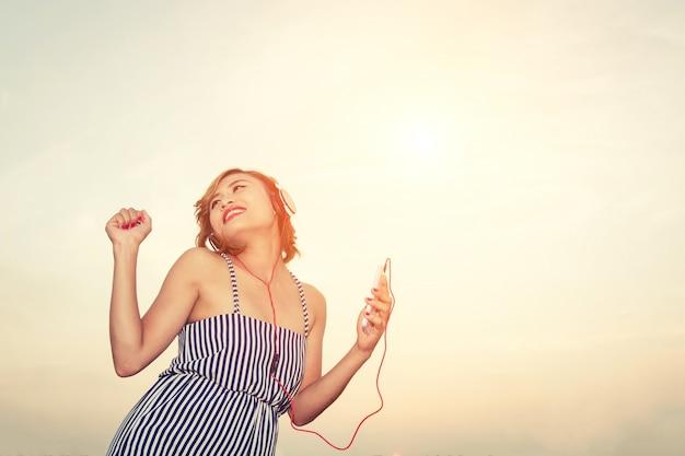 Kobieta słuchania muzyki i tańca na zewnątrz