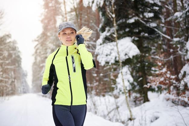 Kobieta, słuchanie muzyki i bieganie w okresie zimowym
