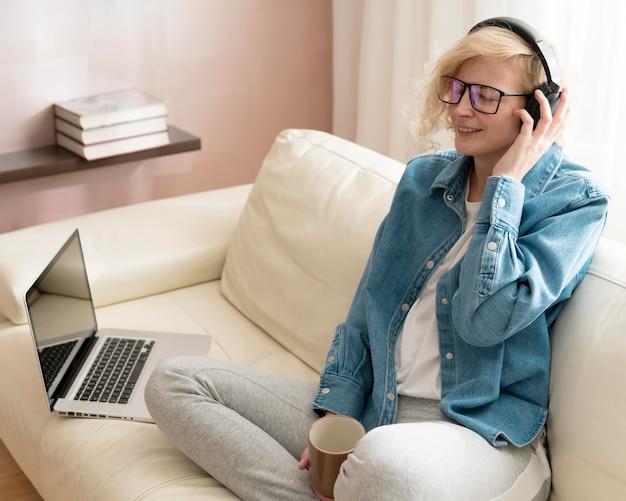 Kobieta, słuchanie muzyki i trzymając kubek kawy na kanapie