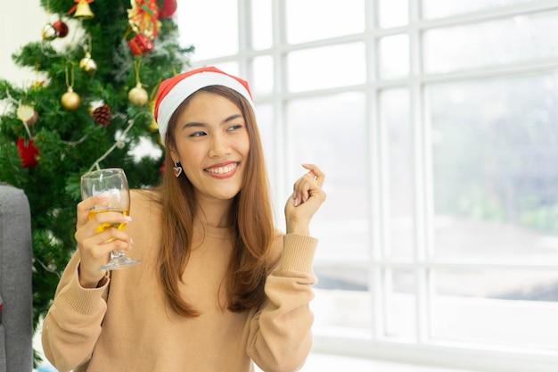 Kobieta słuchanie muzyki, trzymając kieliszek do wina i taniec w salonie