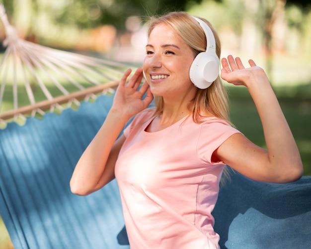 Kobieta, słuchanie muzyki w hamaku