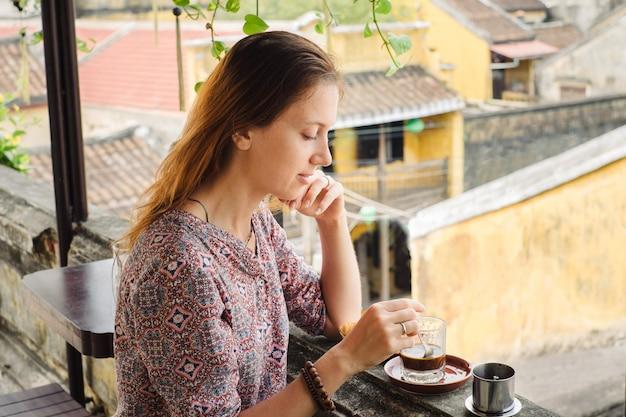Kobieta smakuje wietnamskiej kawy