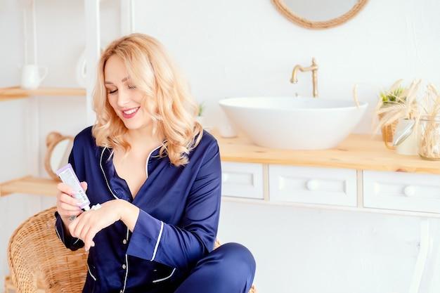 Kobieta smaruje dłonie kremem i wykonuje zabiegi pielęgnacyjne