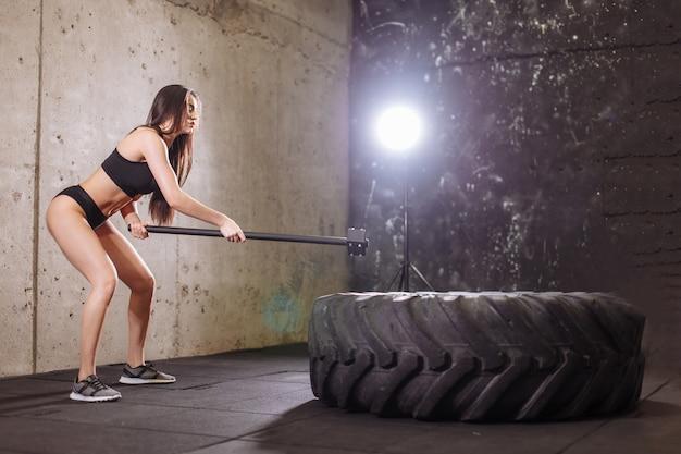Kobieta smashing dużą oponę młotem podczas intensywnego treningu w siłowni fit