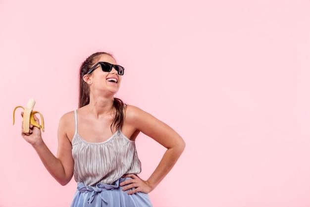Kobieta śmia się banana i trzyma w okularach przeciwsłonecznych