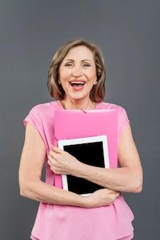 Kobieta, śmiejąc się i trzymając tabletkę