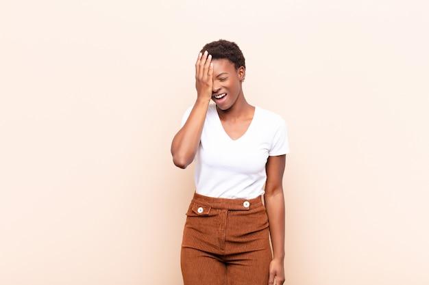 Kobieta śmieje się i bije się w czoło