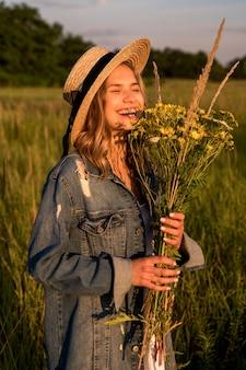 Kobieta śmieje się i trzyma bukiet polnych kwiatów