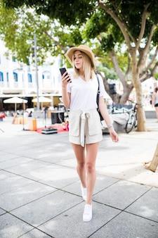 Kobieta sms-y na inteligentny telefon spaceru na ulicy w słoneczny dzień