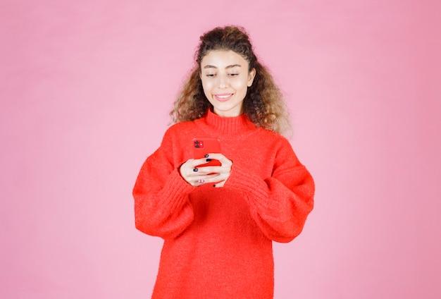 Kobieta sms-y w swoim nowym smartfonie i uczucie szczęścia.