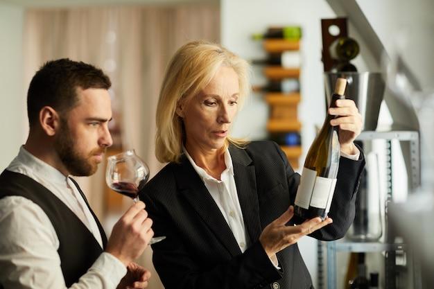 Kobieta sommelier poleca wino