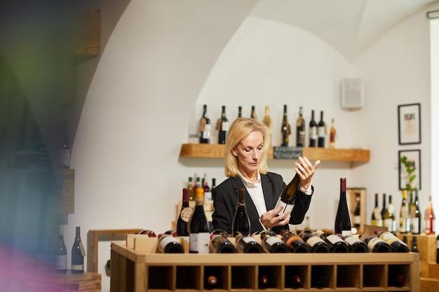 Kobieta sommelier wybiera wino w piwnicy