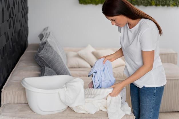 Kobieta sortująca świeżo wyczyszczone ubrania