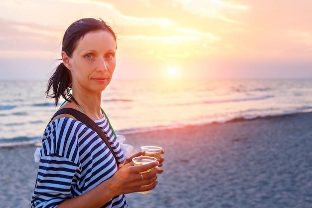 Kobieta spaceru na plaży w surf o zachodzie słońca