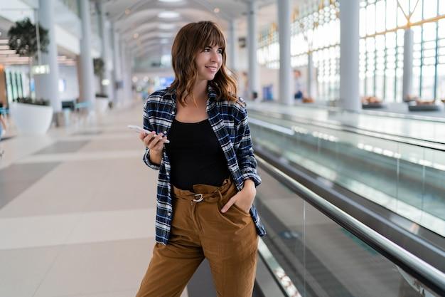 Kobieta spaceru po lotnisku przy użyciu swojego smartfona.