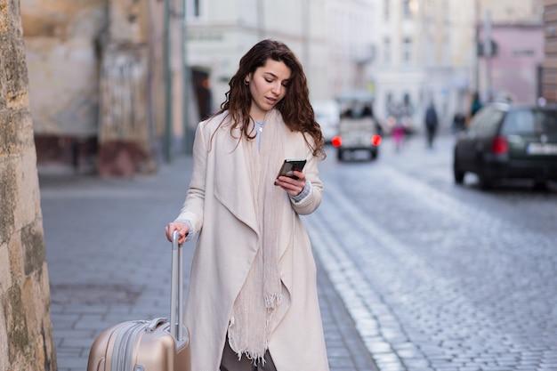 Kobieta spaceru po nowym mieście z telefonem w dłoniach i walizką