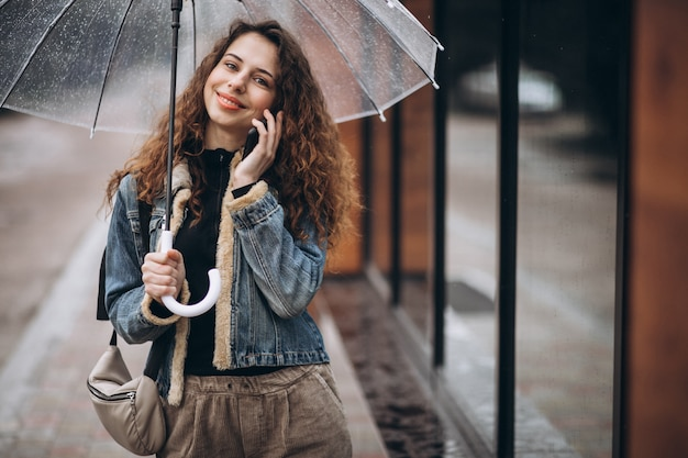 Kobieta spaceru pod parasolem w deszczową pogodę