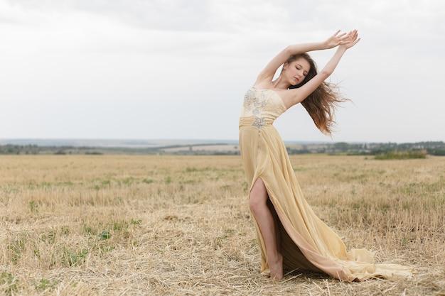 Kobieta spaceru w polu złotej suszonej trawy. naturalne piękno portretu. piękna dziewczyna na polu pszenicy