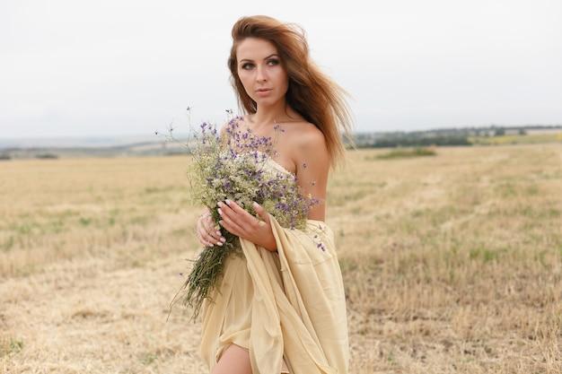 Kobieta spaceru w polu złotej suszonej trawy. naturalne piękno portretu. piękna dziewczyna w polu pszenicy. młoda kobieta w beżowej sukience z bukietem polnych kwiatów.