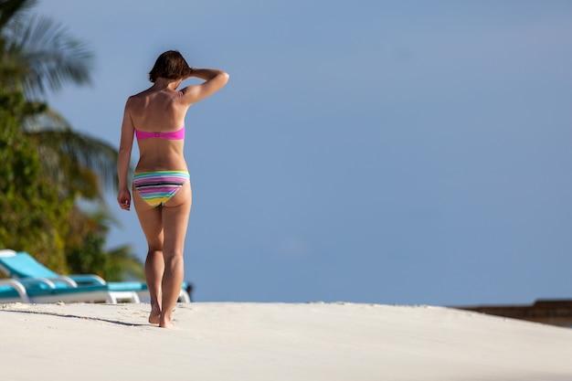Kobieta spaceru wzdłuż plaży w stroju kąpielowym