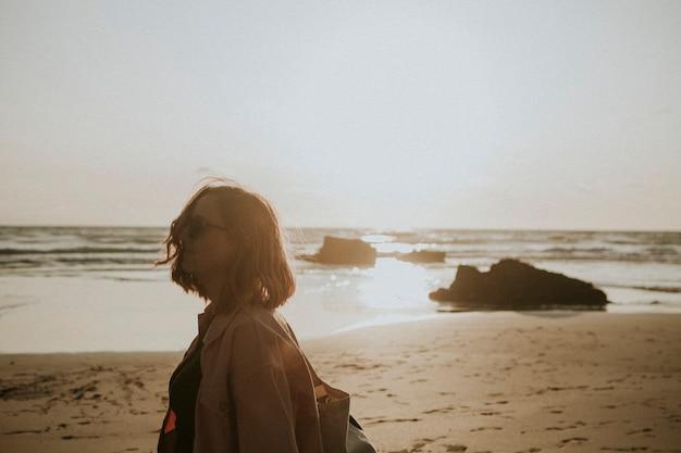 Kobieta spacerująca po plaży o zachodzie słońca