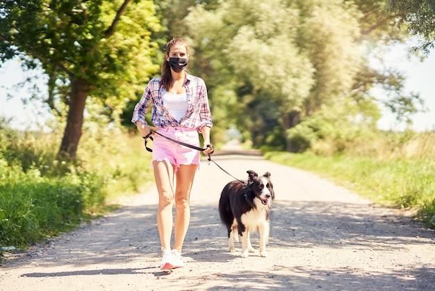 Kobieta spacerująca z psem na wsi i nosząca maskę